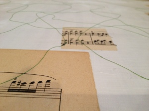 A detail showing squares of sheet music and string adhered to the surface of the plexiglass