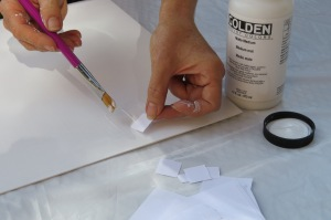 Collaging square paper onto the prepared plexiglass