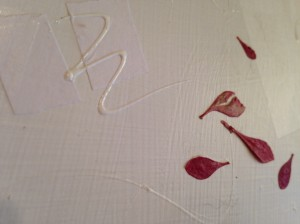 Flower leaves and fabric paint add texture to the canvas.