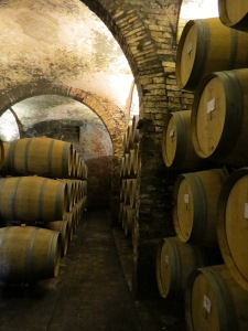 Huge wine barrels line a cellar. Imagine the rich musty smell.
